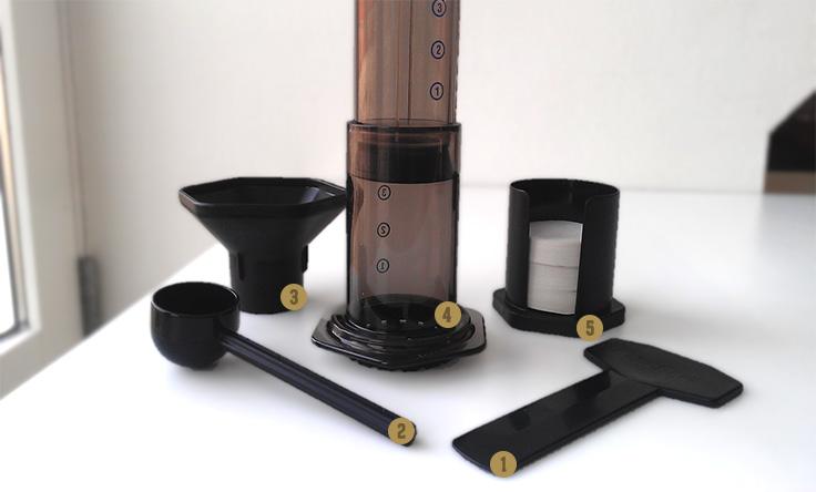 1) Spatel för omrörning. 2) Kaffeskopa. 3) Kaffetratt. 4) Kammaren, pressen och filtret, ihopmonterade. 5) Hållare för pappersfilter.